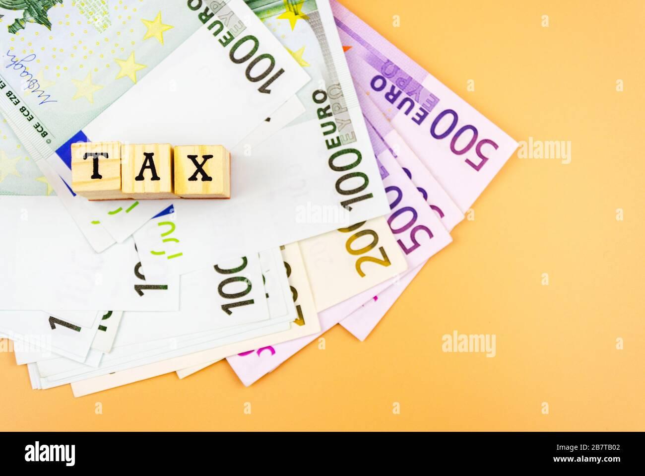 Le mot taxe et la monnaie de l'Union européenne de différentes dénominations sur un fond orange 4 Banque D'Images
