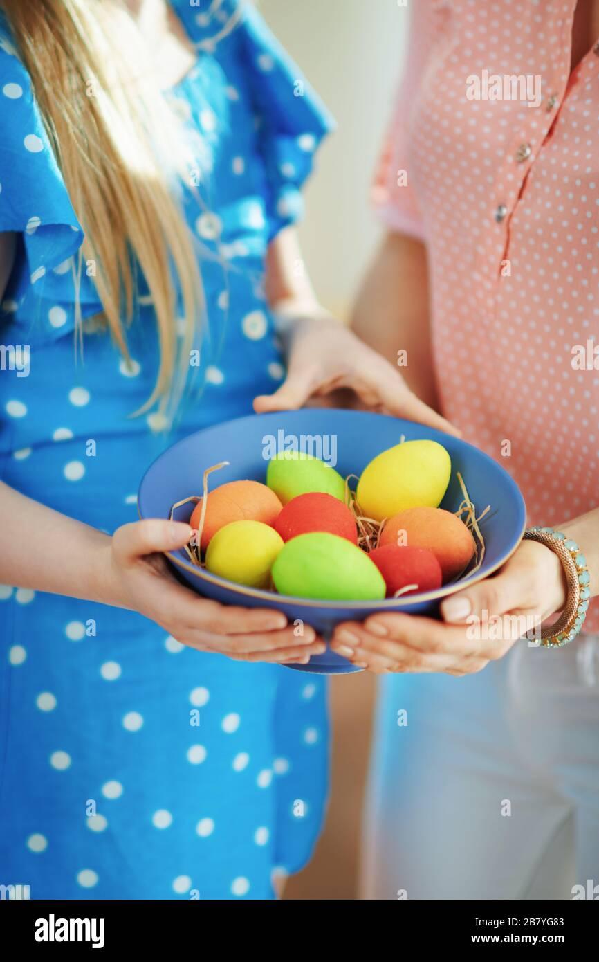 Gros plan sur la mère et l'enfant montrant une plaque bleue avec des œufs de pâques colorés dans le salon en journée ensoleillée de printemps. Banque D'Images