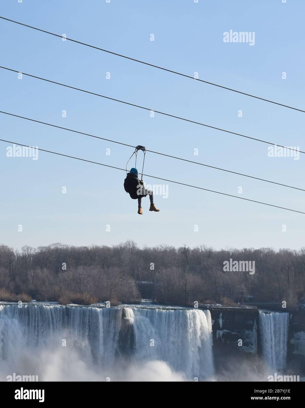 Une personne monte une ligne éclair vers le bas avec la chute d'eau des chutes du Niagara en arrière-plan pour un concept d'activité touristique de vacances. Banque D'Images