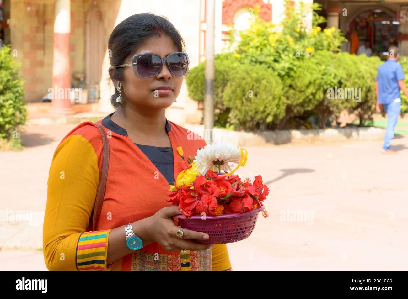 Portrait souriant de la belle jeune adulte traditionnelle mariée Bengali femme tenant un seau de l'offre religieuse des fleurs pendant Durga puja celebrati Banque D'Images