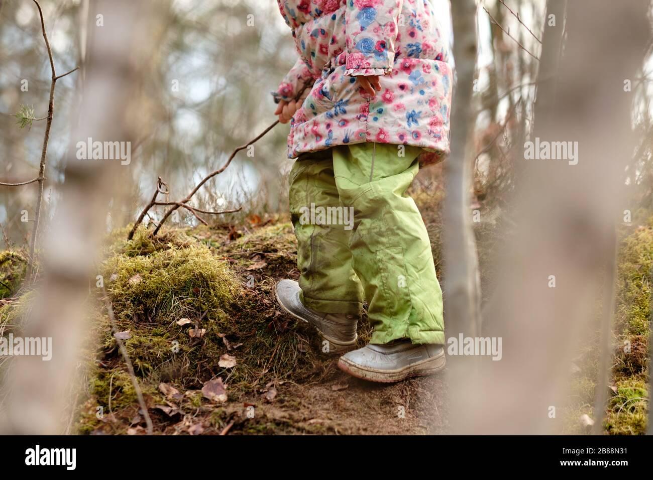 Une petite partie d'une fille caucasienne en vêtements chauds jouant dans la forêt au début du printemps en mars en Allemagne Banque D'Images