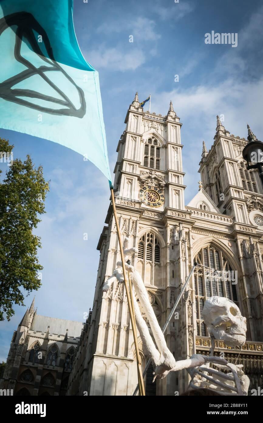 Westminster Abbey, Londres, Royaume-Uni - 9 octobre 2019 - les totêtes de l'extinction des changements climatiques - un faux squelette avec un drapeau des manifestants Banque D'Images