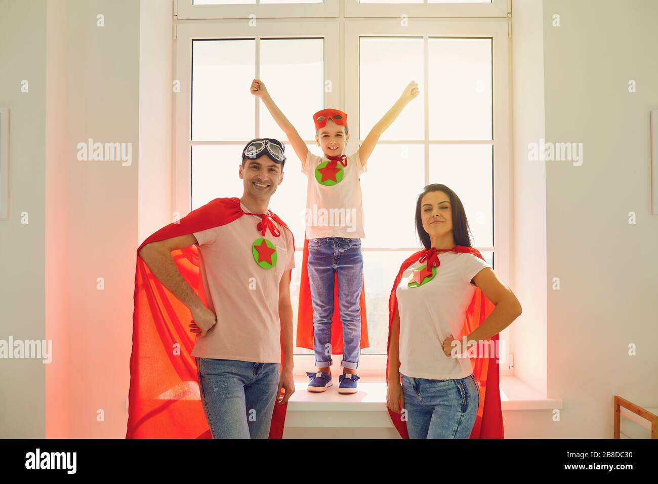 Une famille joyeuse en costume de super héros riant tout en se tenant sur le fond d'une fenêtre dans une salle à l'intérieur. Banque D'Images
