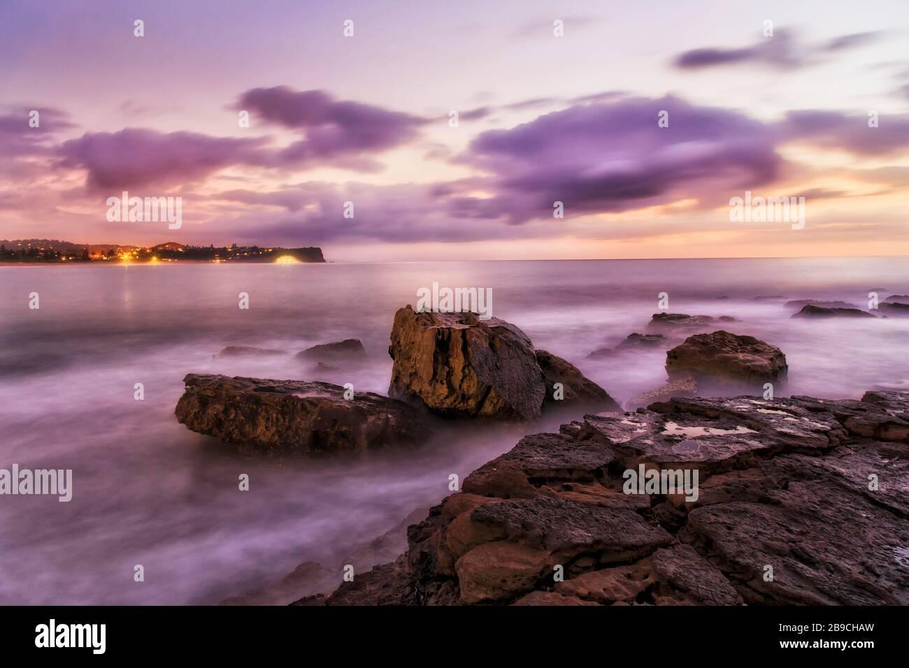 Des roches de grès mouillées de Turimetta se dirigeant sur les plages du nord de Sydney au lever du soleil. Banque D'Images