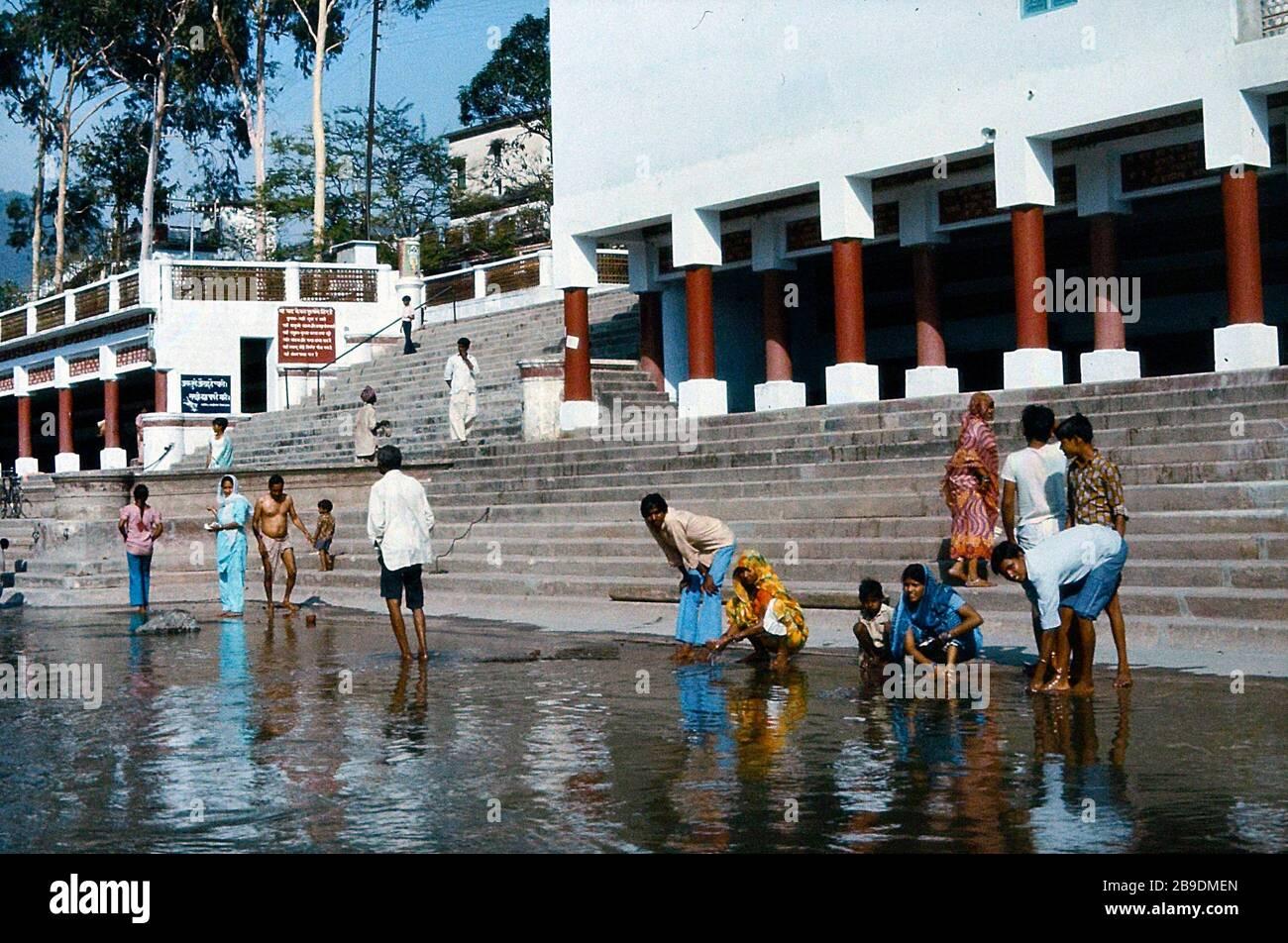 Plusieurs personnes se sont propres dans le Ganges se lavant sur les rives d'une rivière dans une ville en Inde. La banque est fortifiée et peut être atteinte par des escaliers. Sur la banque il y a des bâtiments blancs avec des colonnes rouges. Les femmes, les hommes et les enfants se tiennent ou squatent dans les eaux peu profondes. Les femmes portent des robes lumineuses colorées. [traduction automatique] Banque D'Images