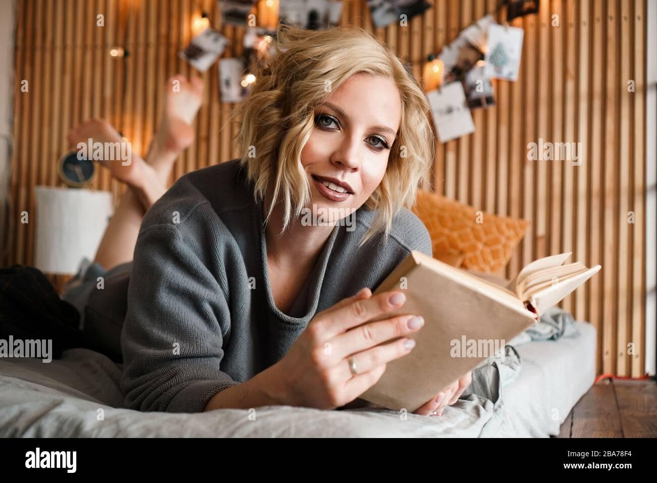 Happy Woman regardant l'appareil photo, livre de détente et de lecture sur un lit confortable - mur en bois et photos avec des lumières - fond flou Banque D'Images