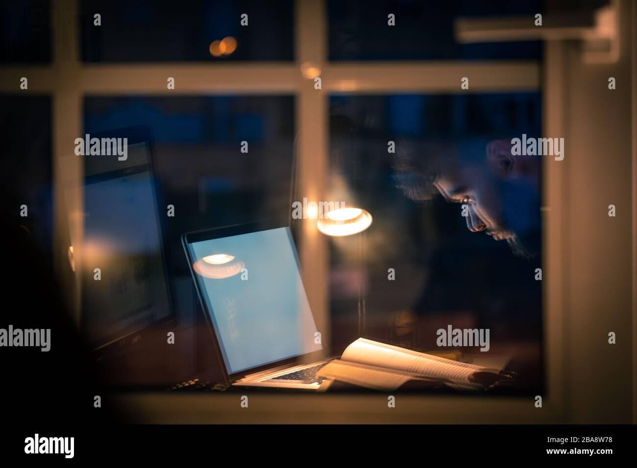 Personne lisant un livre la nuit, reflet de la fenêtre Banque D'Images