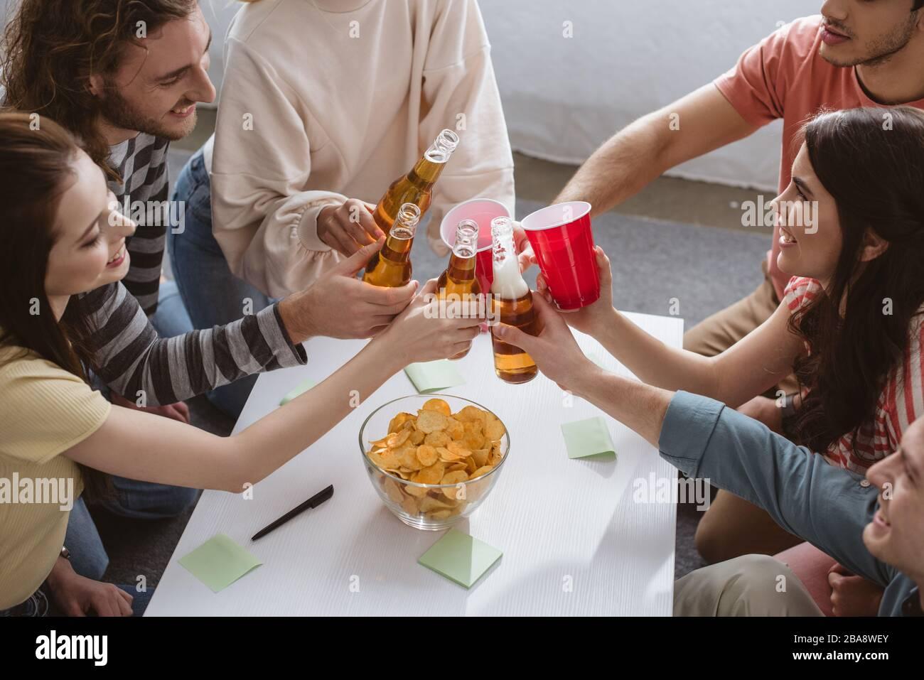 vue en grand angle des amis heureux s'inclinent avec des bouteilles et des tasses tout en jouant le jeu de nom à la maison Banque D'Images