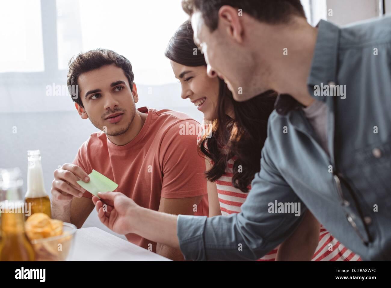 homme sérieux prenant des notes collantes tout en jouant le jeu de nom avec des amis souriants Banque D'Images