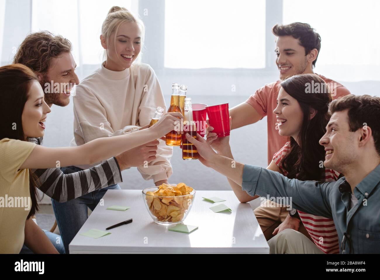 des amis joyeux s'inclinent avec des bouteilles et des tasses en plastique tout en jouant au jeu de nom à la maison Banque D'Images