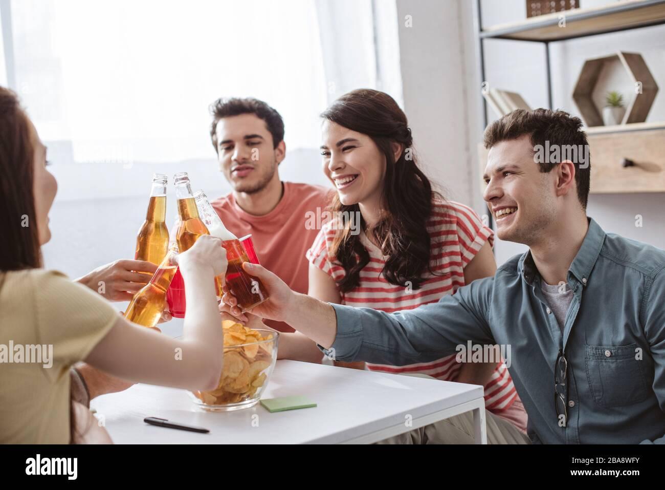 joyeux amis qui s'inclinent avec des bouteilles et des tasses tout en jouant au jeu de nom à la maison Banque D'Images