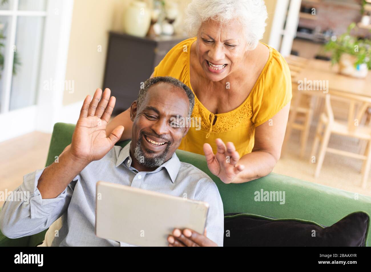 Couple afro-américain senior utilisant une tablette numérique dans un canape Banque D'Images