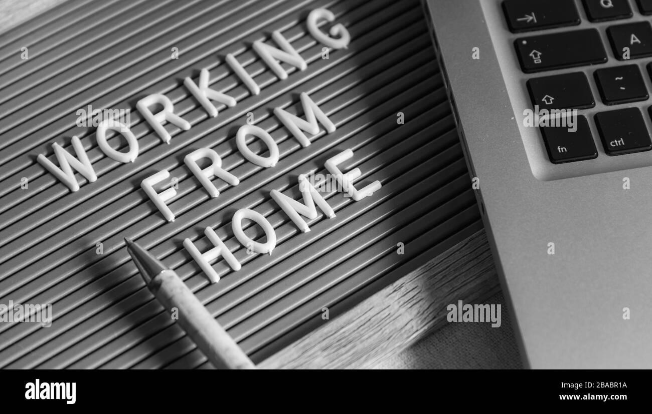 Tableau de composition avec texte « TRAVAILLER À DOMICILE », ordinateur portable et stylo sur le bureau. Travailler à domicile pendant le concept de quarantaine, Covid-19 Banque D'Images