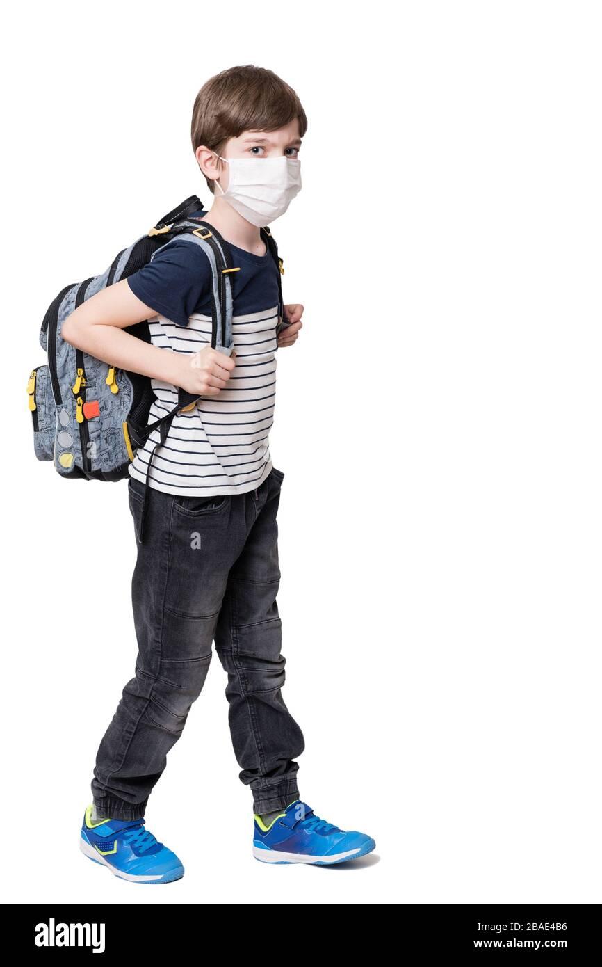 Portrait d'un enfant avec masque de visage tenant le sac scolaire, isolé sur fond blanc Banque D'Images