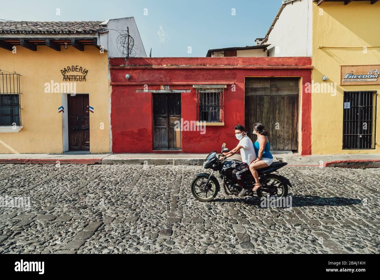 Couple sur leur moto portant des masques de visage pendant la pandémie de coronavirus. Rues vides dans la ville coloniale colorée d'Antigua Guatemala Banque D'Images