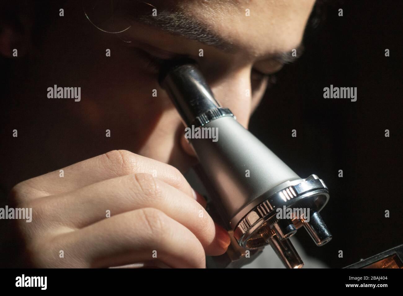 Jeune étudiant en sciences faisant de la recherche regardant par son microscope tard dans la nuit à sa maison Banque D'Images