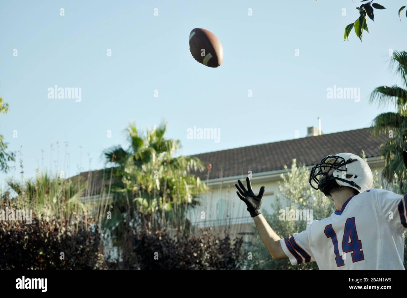Joueur de football américain dans un jeu. Joueur qui attrape un ballon de football américain dans un parc. Banque D'Images