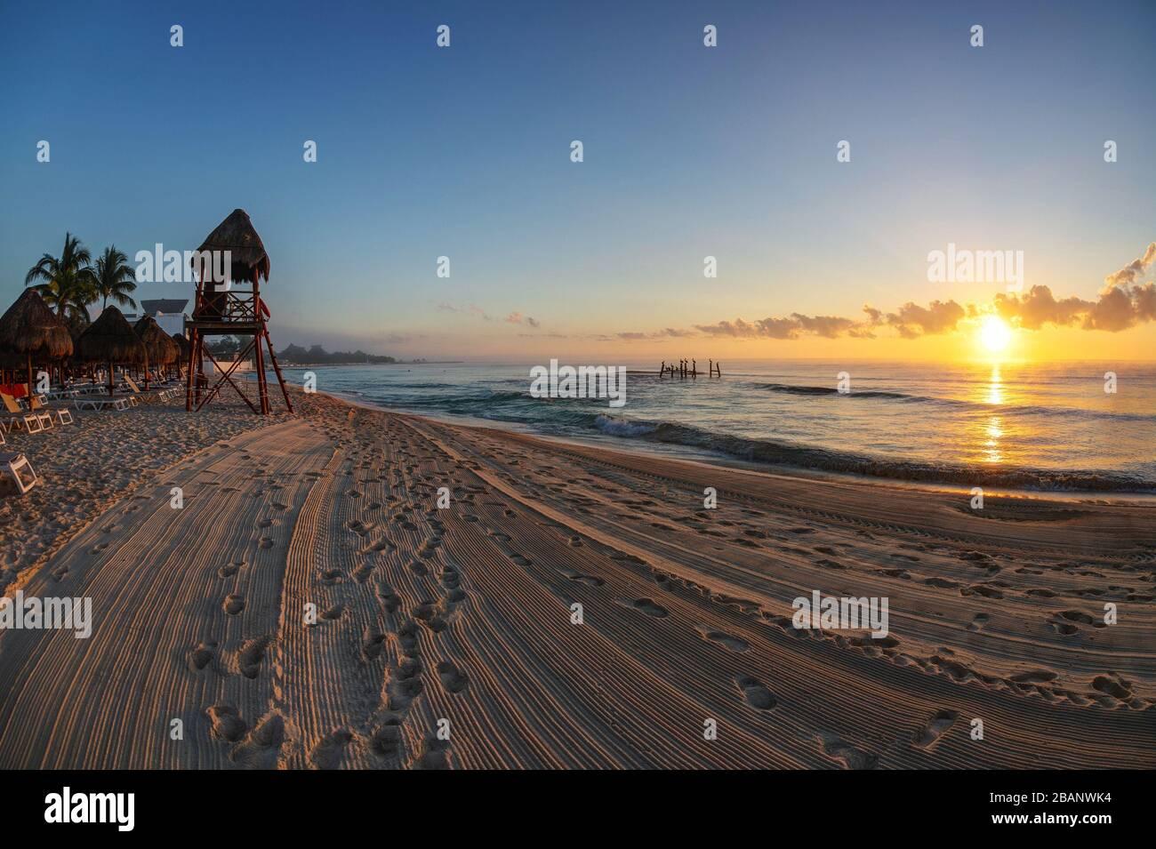 Lever de soleil doré sur les plages tropicales de la Riviera Maya près de Cancun, Mexique, avec tour de sauveteur surplombant la mer des Caraïbes. Banque D'Images