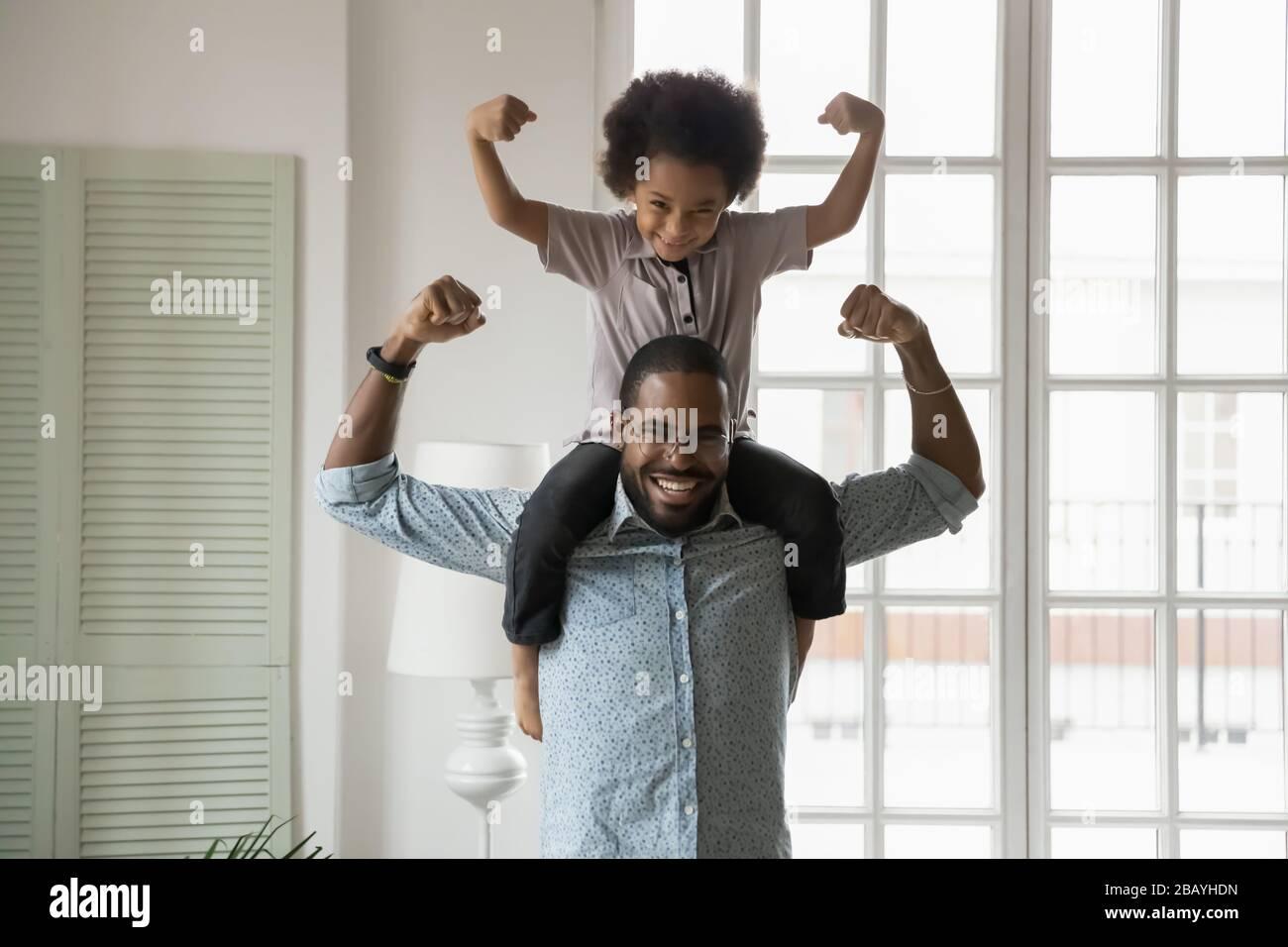 Ethnicité africaine petit fils assis sur les épaules des pères montrant des biceps Banque D'Images