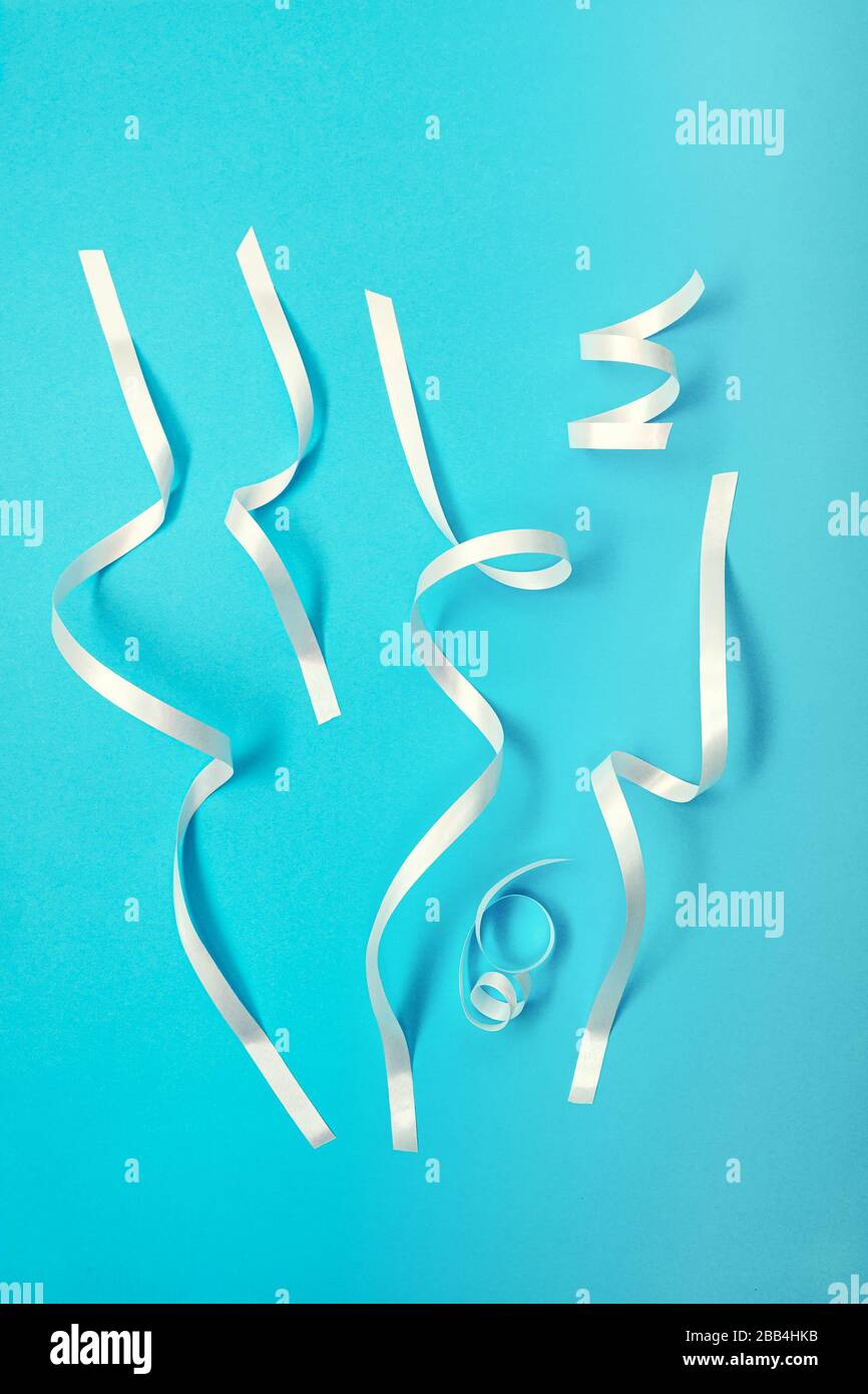 Bandes confettis blanches sur fond bleu Banque D'Images