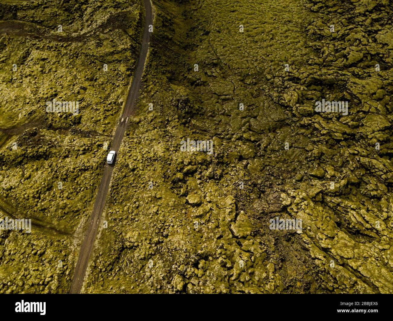 Vue aérienne de la voiture traversant des roches de lave couvertes de mousse dans l'IC Banque D'Images