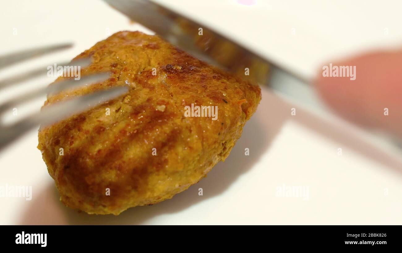 Gros plan sur la viande. Couteau de table et fourche. Viande hachée. Graisse mincemat. Coupe frite simple en plaque blanche, fourche et couteau Banque D'Images