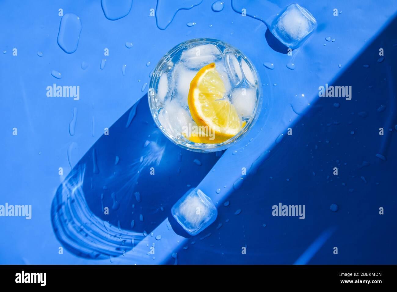 Un verre d'eau rafraîchissante avec de la glace et du citron sur un fond bleu. Concept de chaleur, frais. Lumière naturelle. Couche plate, vue supérieure, espace de copie Banque D'Images