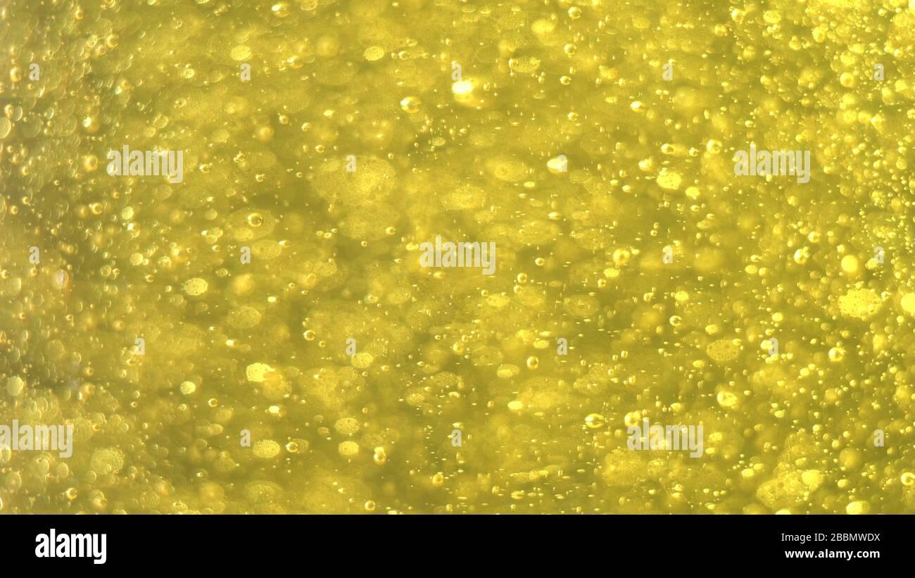 Les bulles d'or augmentent lentement. Fond doré. De grandes et petites bulles d'or s'huilent à l'intérieur du liquide d'or Banque D'Images