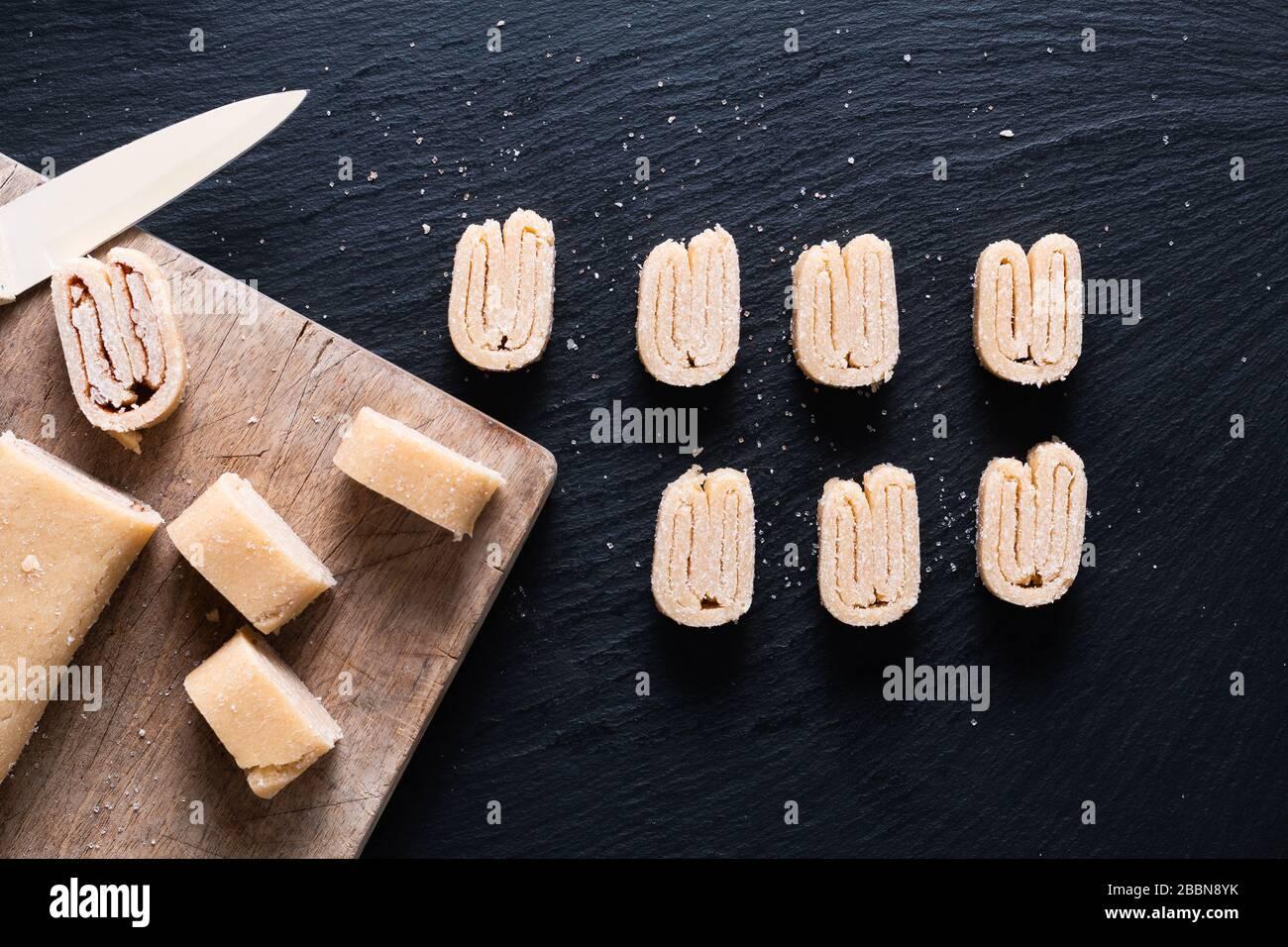 Concept alimentaire pâte feuilletée bio maison pour les palmiers français, les pâtisseries chinoises aux papillons ou les oreilles d'éléphant sur tableau noir en ardoise Banque D'Images