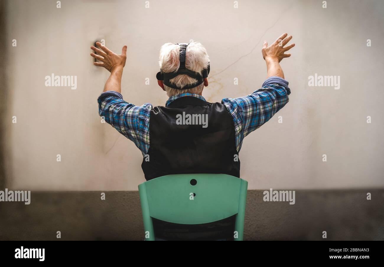 l'homme mûr regarde à travers le spectateur de la réalité virtuelle pendant la quarantaine difficile au moment du coronavirus Banque D'Images