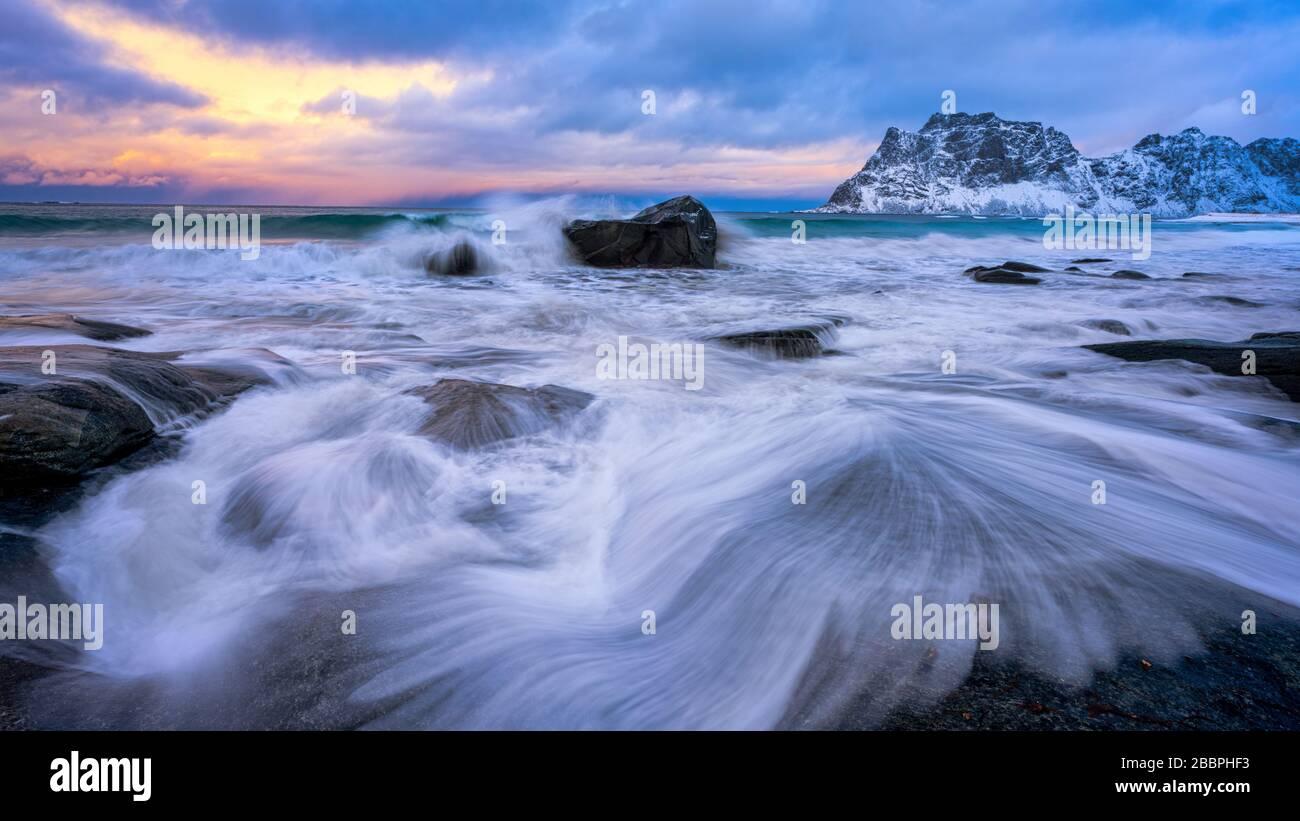 Vagues de l'océan se lavant au-dessus des rochers côtiers avec le ciel coucher du soleil en arrière-plan Banque D'Images