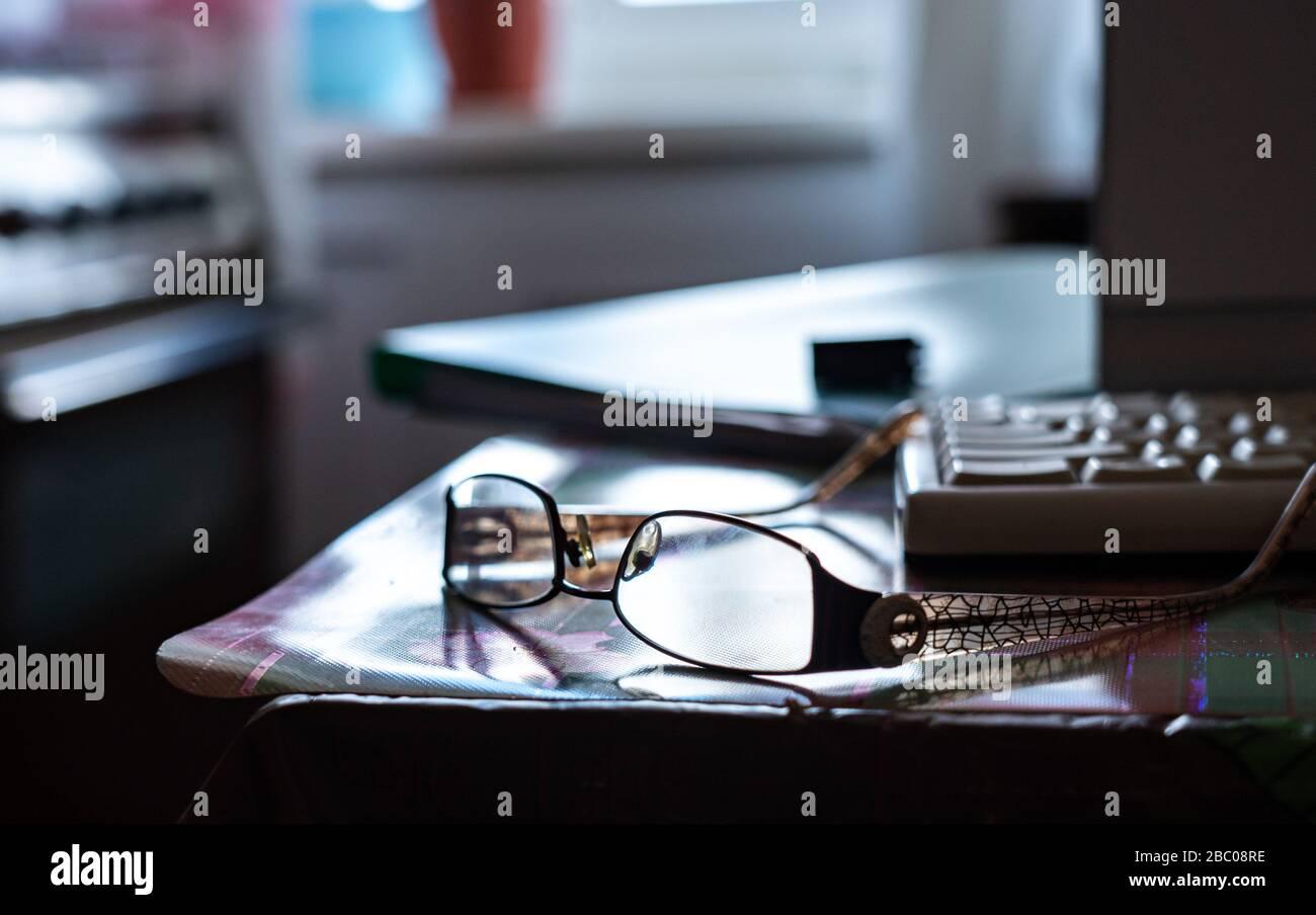 Travailler à domicile. Travail à distance via Internet. Lunettes et clavier sur la table de cuisine Banque D'Images