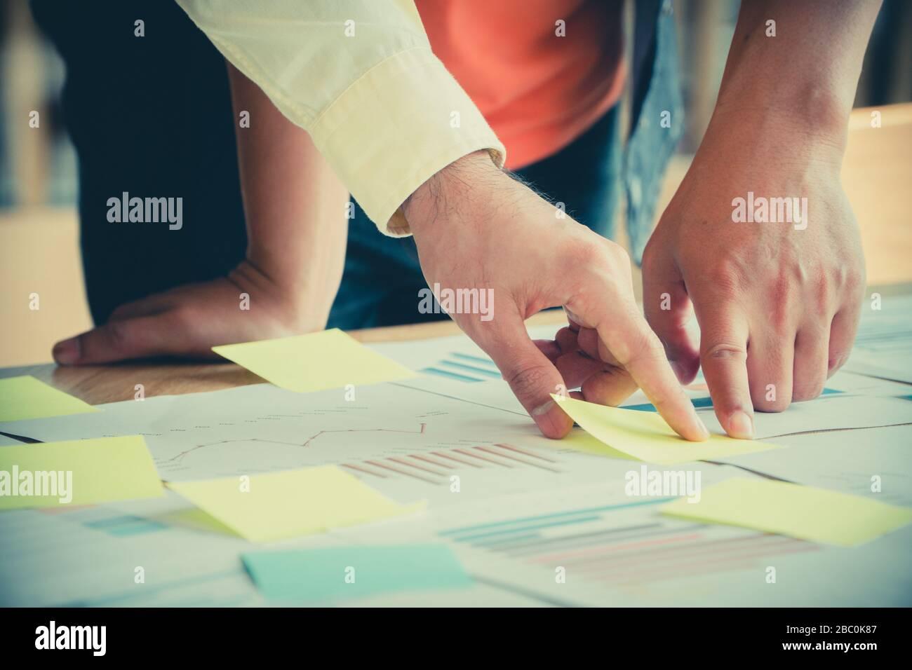 Groupe de gens d'affaires réunion permanent avec des collègues dans la salle de réunion et d'afficher le graphique de rendement annuel d'analyser et d'anticiper les t Banque D'Images