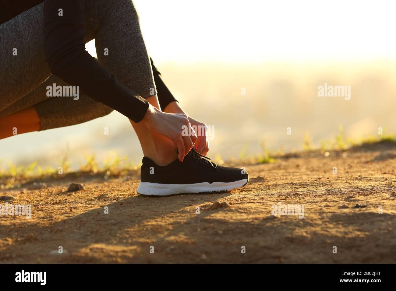 Vue latérale près de la femme de coureur mains nouant des lacets de chaussures sur le sol au coucher du soleil Banque D'Images