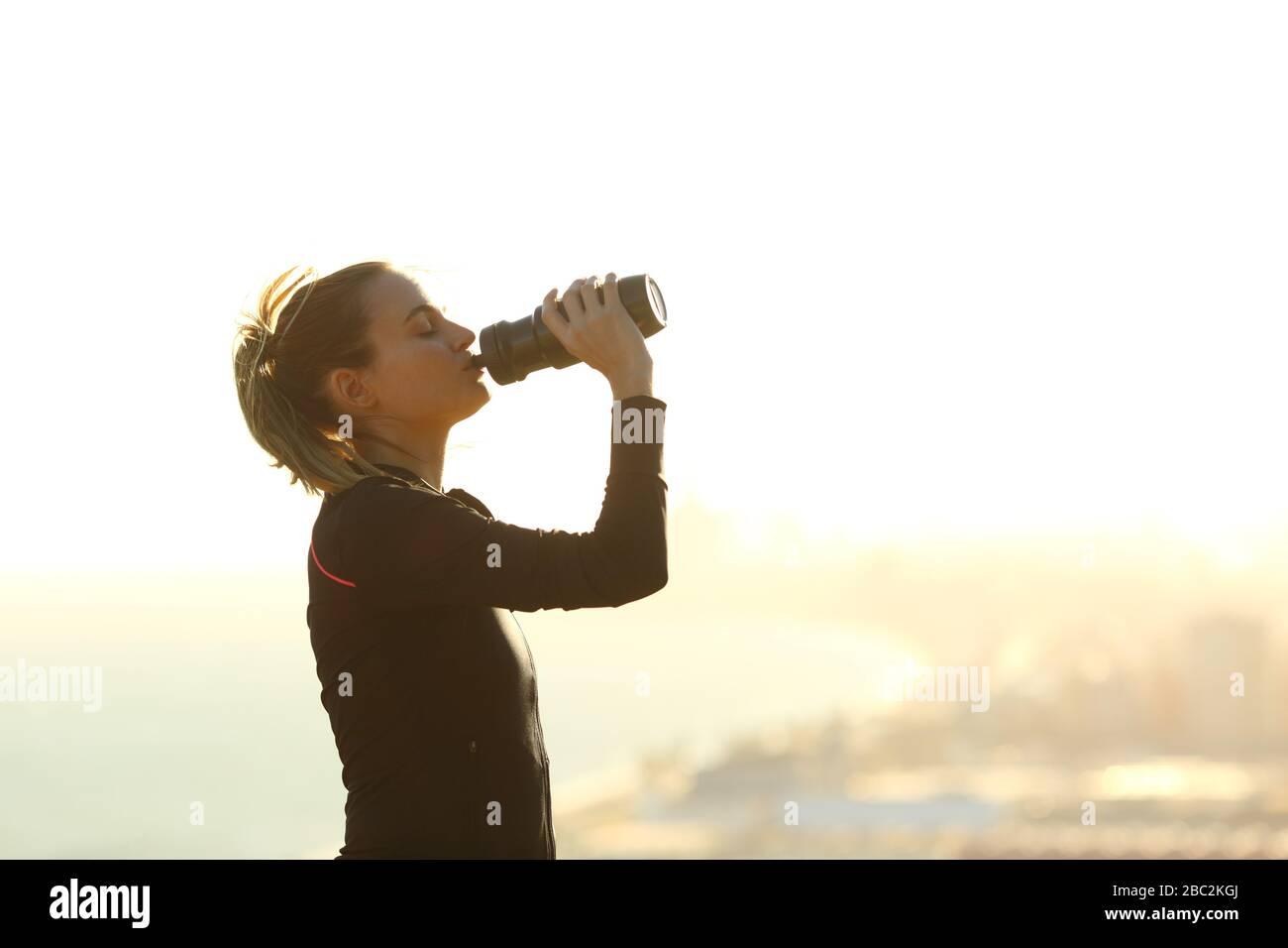 Vue latérale portrait d'une femme de coureur buvant de l'eau à partir d'une bouteille hydratante après l'exercice dans une périphérie de la ville Banque D'Images