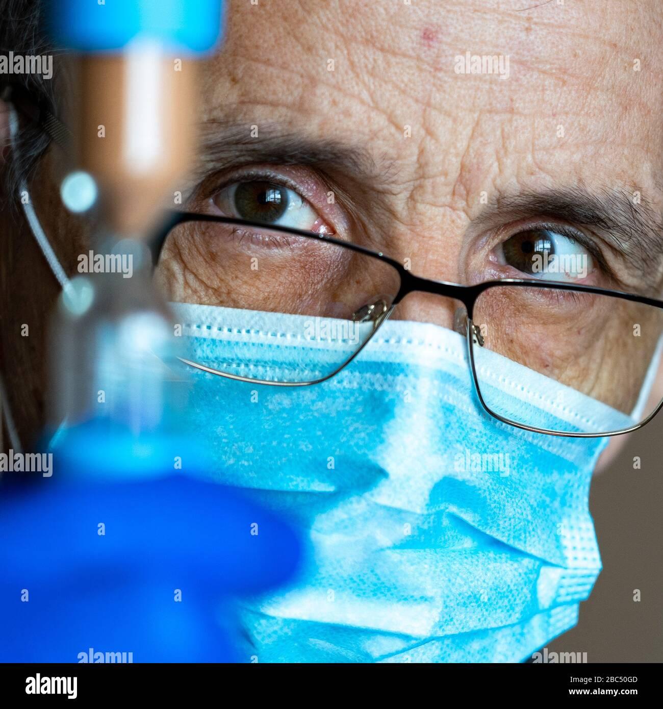 Un médecin fatigué avec des lunettes et un masque regarde le sablier. Banque D'Images
