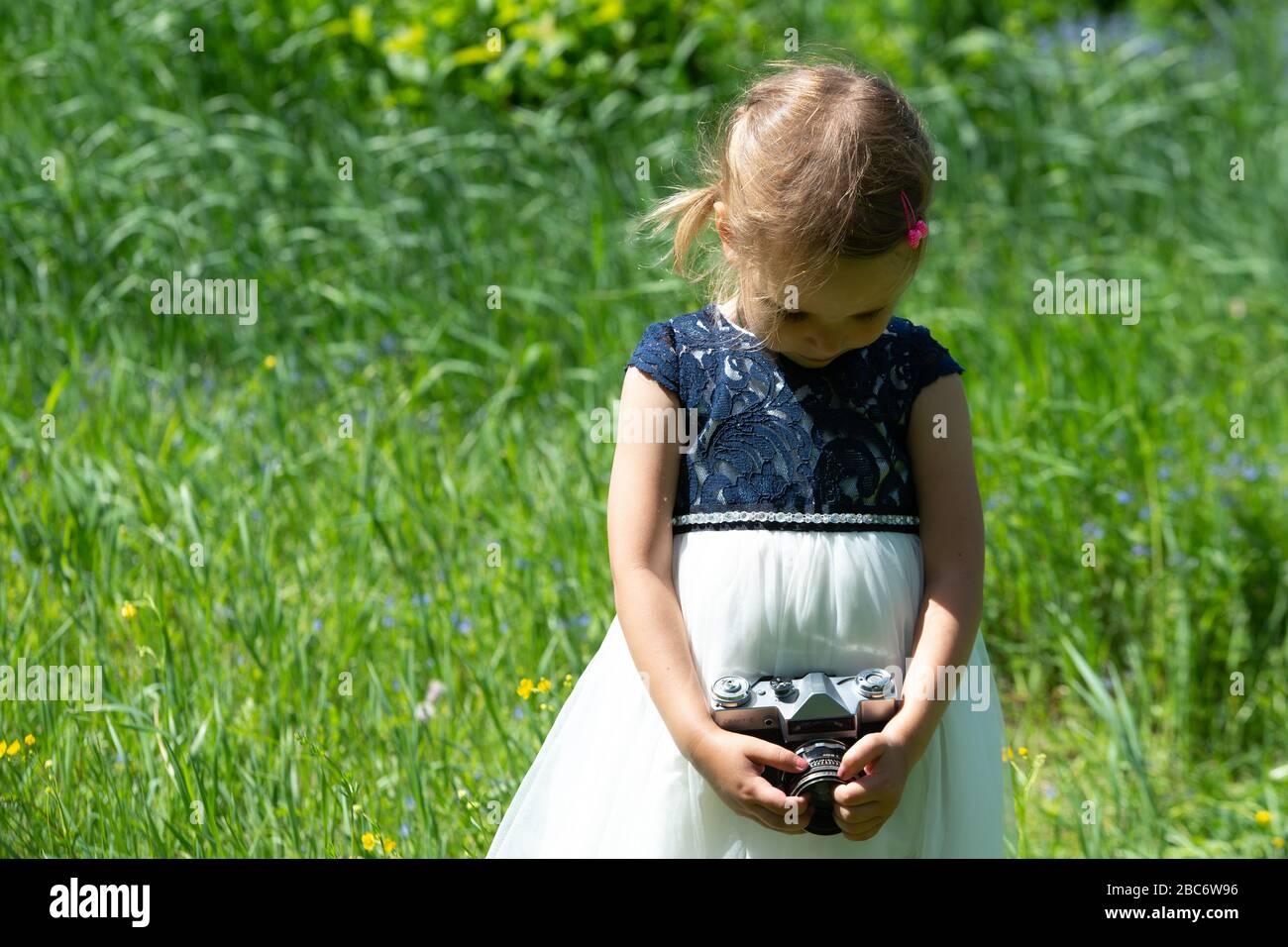 Petite fille mignonne dans une robe légère tenant un appareil photo rétro vintage dans une triste humeur. Petite fille avec un appareil photo rétro dans le parc en été. Banque D'Images