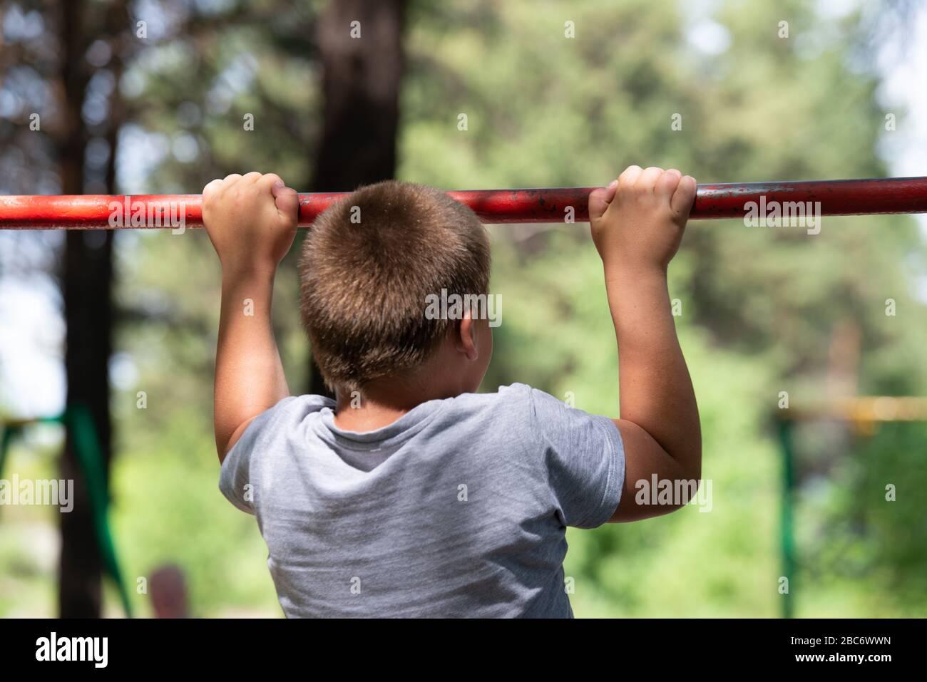 le garçon s'arrache sur la barre transversale Banque D'Images