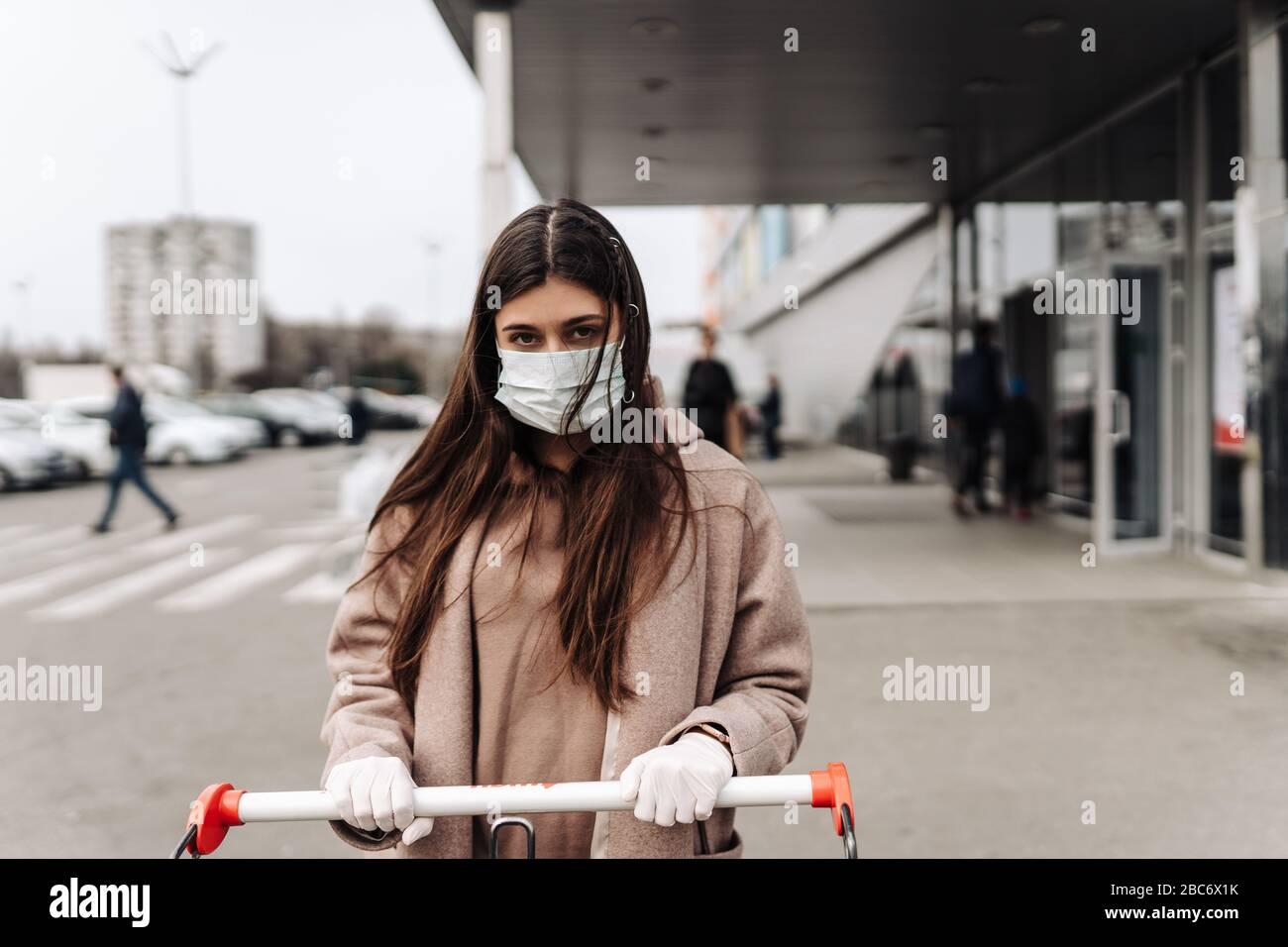 Jeune femme portant un masque de protection contre le coronavirus 2019-nCoV poussant un panier. Banque D'Images