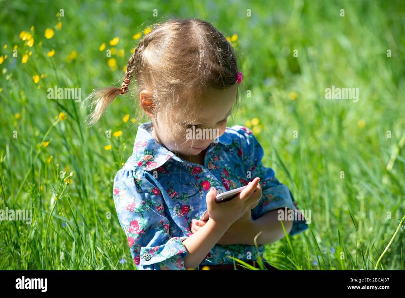 Petite fille avec queue de porc lors d'une journée d'été ensoleillée sur un pré vert Banque D'Images
