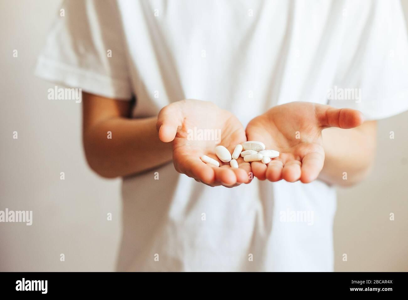 Gros plan des pilules de main. Main d'enfant avec pilules Banque D'Images