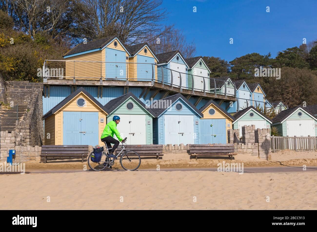 Bournemouth, Dorset Royaume-Uni. 4 avril 2020. Les plages de Bournemouth sont principalement vides à part ceux qui visitent la mer pour faire leur exercice autorisé, comme les visiteurs ont conseillé de rester à la maison et de respecter les restrictions de Coronavirus pour les distanciation sociale, avec des parkings fermés pour dissuader les visiteurs de conduire à l'afar. Les cyclistes longent la promenade en passant devant les huttes de plage à Alum Chine alors que le soleil sort et le ciel bleu - homme à vélo d'équitation. Crédit: Carolyn Jenkins/Alay Live News Banque D'Images
