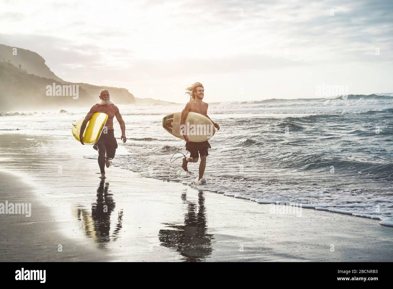Des amis de plusieurs générations qui vont surfer sur la plage tropicale - des familles qui s'amusent à faire du sport extrême - des personnes âgées joyeuses et un concept de mode de vie sain Banque D'Images