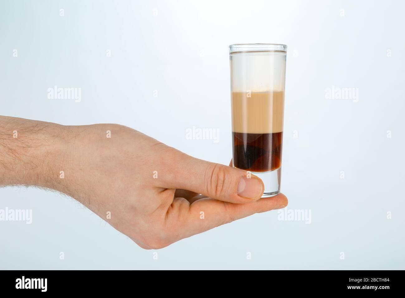 Gros plan d'une main tenant un verre de cocktail en forme de b52 sur fond blanc avec espace de copie. Banque D'Images
