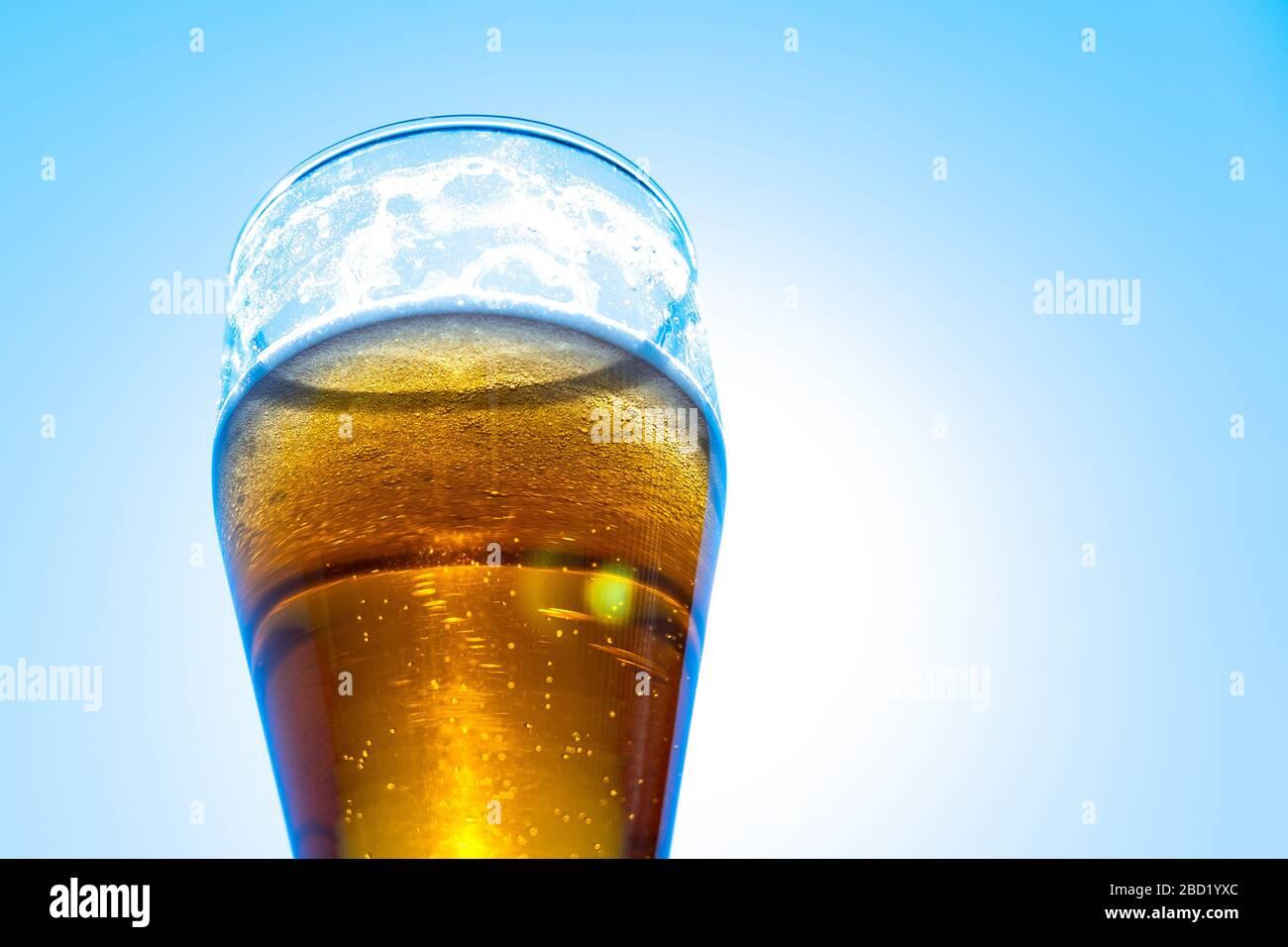 Bière légère dans un gobelet en verre sur un fond de ciel bleu. Mousse de bière sur les murs d'un verre au soleil. Banque D'Images