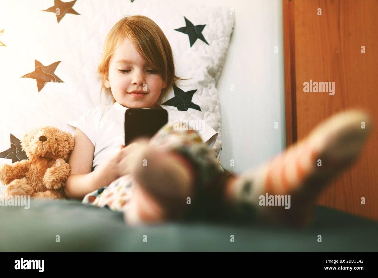 Jolie petite fille souriante avec smartphone dans les mains. Concept de chat vidéo, de regarder des vidéos ou de jouer à des jeux. Banque D'Images