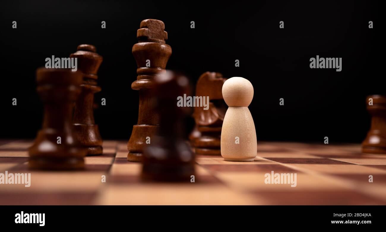 Les personnages en bois (homme d'affaires) qui se tiennent face au roi des échecs et qui sont dans le cercle des échecs. Les nouveaux acteurs commerciaux sont confrontés à des défis. La direction Banque D'Images