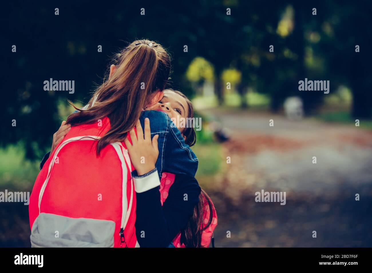 Deux amis de l'école embrassant, rencontrer dans le parc. Marcher les uns dans les autres avec des bras ouverts et sourire. Le concept de l'école, de l'étude, de l'éducation, de l'amitié, Banque D'Images