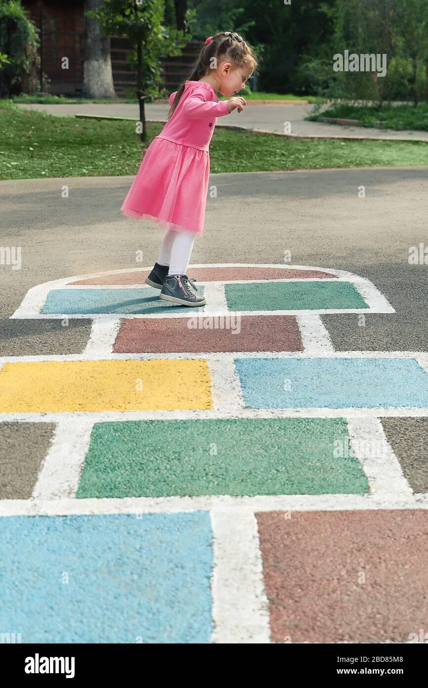 Jeune fille mignonne jouant au hopscotch sur l'arrière-cour Banque D'Images