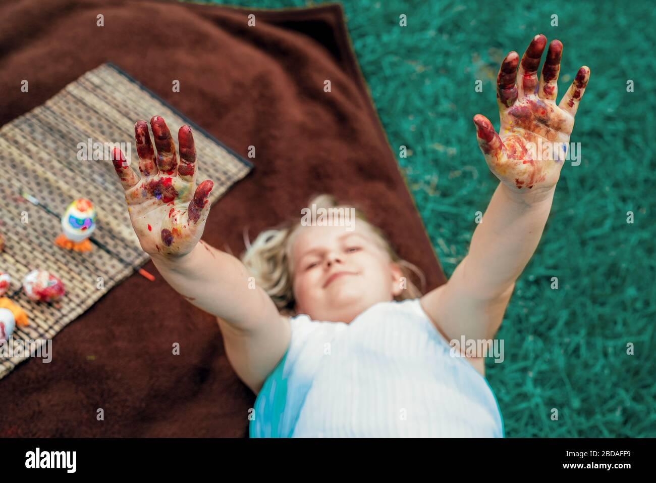 Mignonne petite fille layong sur la couverture sur l'herbe dans l'arrière-cour et montrer sa sale avec des mains peintes, peindre des œufs de Pâques. Banque D'Images